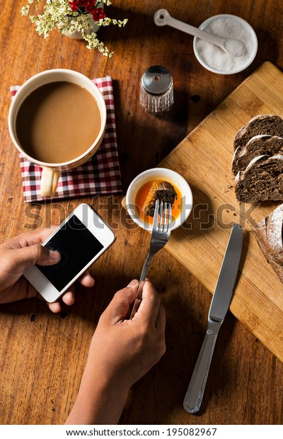 Unrecognizable man eating appetizer while using smartphone, view from above