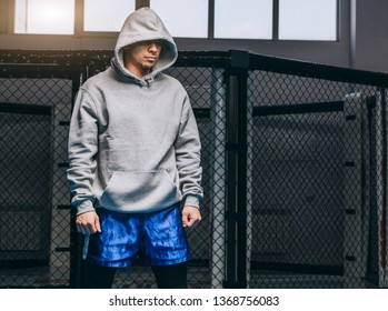 Unrecognizable man in grey hoodie with hood down over his eyes and blue boxing shorts posing at boxing club