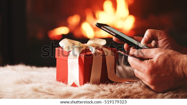 Unrecognizable Man Hands holding Credit Card and Using SmartPhone by the Burning Fireplace and Festive Presents - Close Up. Man with phone key-green screen by cozy fireside.
