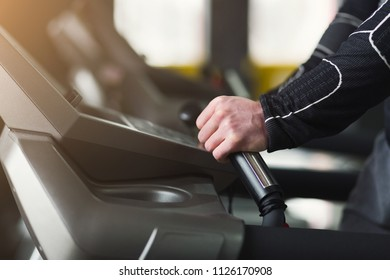 Unrecognizable man hands on elliptical trainer handrails in sport club. Cardio workout background, running on treadmill. Healthy lifestyle, guy training in gym, side view, copy space