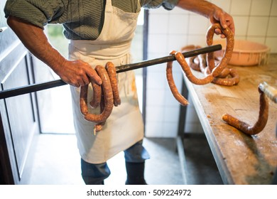Unrecognizable man hanging homemade raw sausages on wooden stick