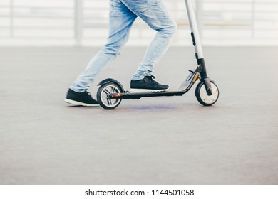 Unrecognizable man has active lifestyle, rides electric scooter, has hobby, rests as has weekend. People, hobby and driving concept