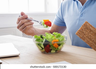 Unrecognizable man has healthy business lunch in modern office. Businessman in t-shirt at working place with vegetable salad in bowl and fork in hand, diet and eating right concept. High key