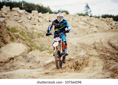 Unrecognizable man in helmets and gear riding a motorcycle on the sand