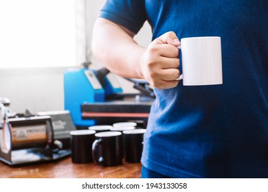 unrecognizable man holding awhite cup behind a bottom where there are cups and adesign sublimation machines.