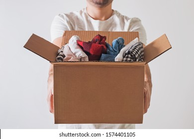 Unrecognizable man holding a cardboard box full of clothes close-up. Clothing donation.