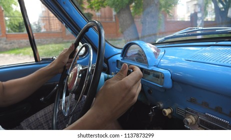 Unrecognizable man holding hands on a steering wheel and drives a retro car in the city on summer day. Young guy inside his old blue automobile. Close up Side view Slow motion.
