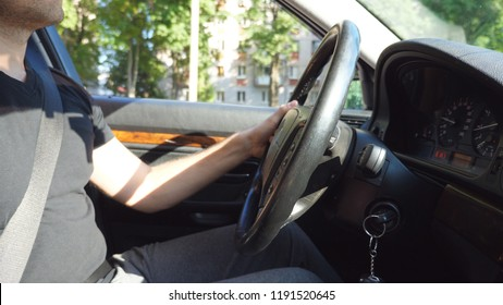 Unrecognizable man holding his hand on a steering wheel and drives a car on the urban road on sunny summer day. Young guy rides on his car. Close up Side view Slow motion.