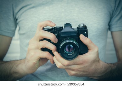 Unrecognizable man is holding an old photocamera