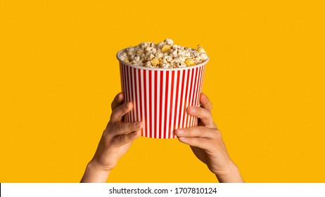 Unrecognizable man holding striped paper bucket with popcorn on orange background, closeup. Panorama