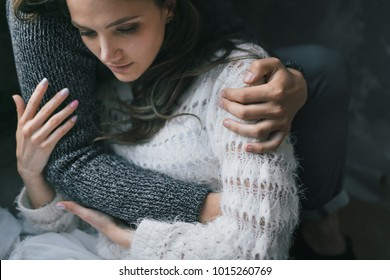 Unrecognizable man hugs his beautiful woman. Sensitive couple in love. Close-up portrait. Indoors