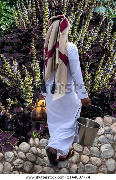 Unrecognizable man in national Qatar clothes is carrying a metal bucket and copper teapots walking on a garden path in a flowering garden.