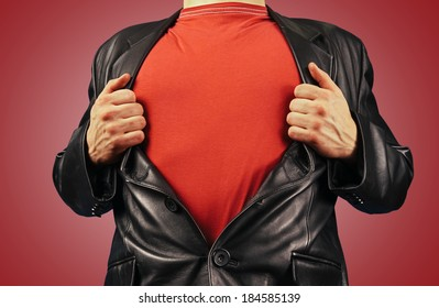 Unrecognizable man opens suit showing red t-shirt on a red background