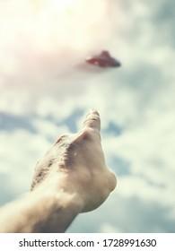 Un homme méconnaissable pointe vers un objet volant non identifié dans le ciel, une image tonique du point de vue. Idée de la Journée de l'OVNI