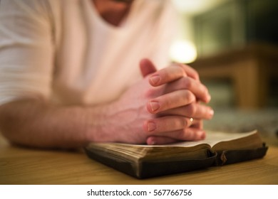 Unrecognizable man praying, kneeling on the floor, hands on Bibl