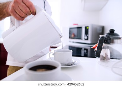 Unrecognizable man preparing coffee. Pouring water into a cup.