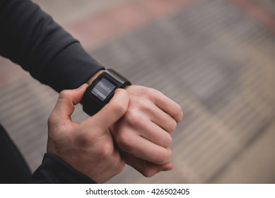 Unrecognizable man pushing button on sport wristwatch with text ready.from above