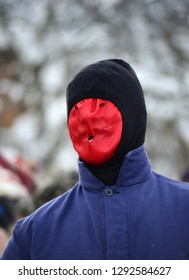 unrecognizable man with red mask and hat on a canival