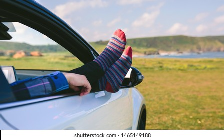 Unrecognizable man resting with his feet up sitting on the passenger seat of the car