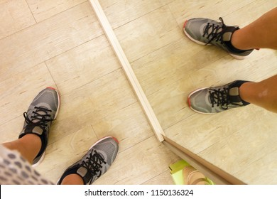 Unrecognizable man standing in front of mirror on wooden floor wearing grey sporty trainers shoes. Sport footwear concept.