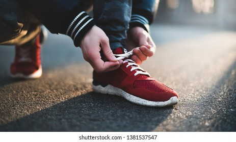 982c8764f6f5a Unrecognizable man stopping lacing shoe outdoors. Athletic shoes concept.  Jogging in the park