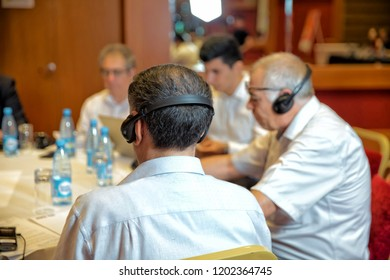 Unrecognizable man using headphones for translation during video conference . Group of business people attending press conference or presentation.