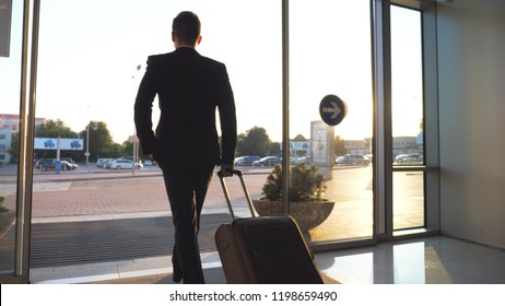 Unrecognizable man walking through glass automatic door of modern airport to city street and pulling suitcase on wheels. Businessman going from terminal to cars parking with his luggage. Rear view.