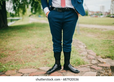 Unrecognizable man in wedding suit standing outdoor with socks put on trousers. Groom in black leather shoes standing on nature at stone. Freaky, foolish, absurd, odd clothes style. Funny marriage day