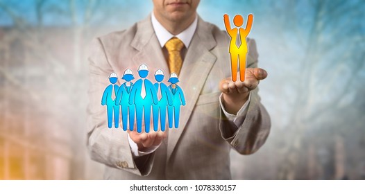 Unrecognizable manager lifting up a cheering white collar employee above a group of blue collar workers. Business concept for mediation, conflict management, labor dispute, education, success.