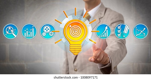 Unrecognizable marketing manager in gray suit is presenting a bright targeting idea represented by an arrow hitting target inside a lightbulb. Business concept for goal setting, success planning.