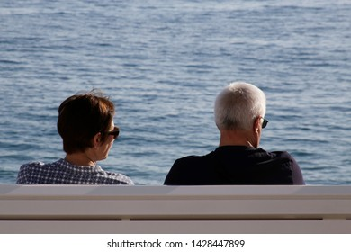 Unrecognizable mature couple sits together close to each other on bench at seashore or ocean beach. Old man and woman in their 60s or 70s in concept of people in love, friendship, leisure or lifestyle