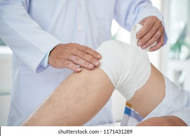 Unrecognizable medical practitioner wrapping bandage around knee of crop patient in doctor's office