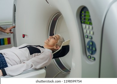 Unrecognizable medical technician pressing buttons on the CT scanner while senior woman is lying on the CT scanner bed.