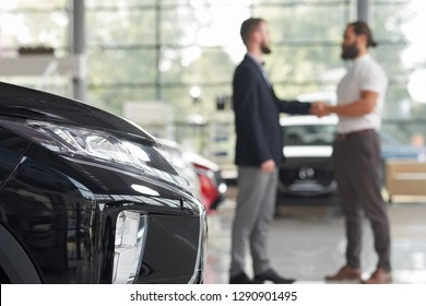 Unrecognizable men shaking hands, standing in modern car showroom. Black car headlight. Car dealer and client of car center making deal. Client purchasing new vehicle.