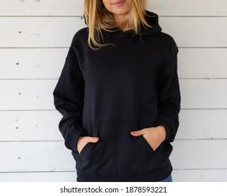 Unrecognizable model in black hoodie sweatshirt. Fashion mockup.