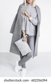 Unrecognizable model wearing casual outfit and holding clutch bag. Gray clothing in trendy minimalistic style. Street fashion for spring or fall season. Details of everyday elegant look.