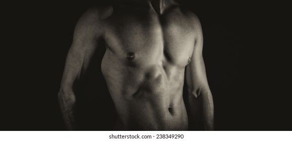 Unrecognizable muscular male body. Black and white.