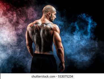 Unrecognizable muscular man with tattoo on back against of smoke background. Isolated.