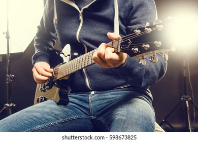An unrecognizable musician sitting and playing the guitar. Horizontal studio shot.