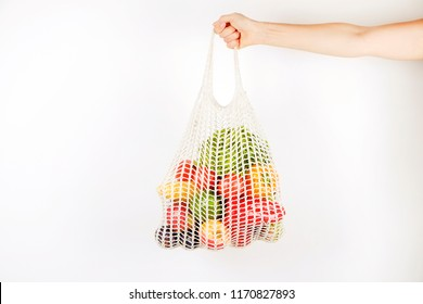 Unrecognizable oung woman's hand holding a bag of mixed fruit, vegetables & greens: corn cob, tomato, pepper, lettuce, pear & apple. Zero waste concept. White wall background, copy space, close up.