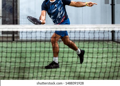 unrecognizable padel player playing padel in a green grass padel court indoor behind the net