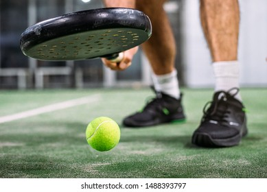 unrecognizable padel player taking the padel ball in a green grass padel court indoor