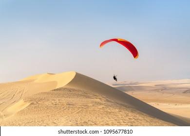 Unrecognizable paraglider flying over sand dunes in Qatar desert