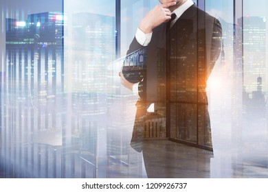 Unrecognizable pensive businessman standing over night cityscape background. Toned image double exposure mock up