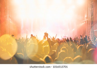 Unrecognizable people at concert. Stage lights, colorful effects.