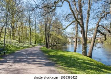 Unrecognizable people enjoy spring atmosphere in the city park along Motala river in Norrkoping, Sweden