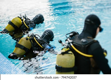 Unrecognizable people in equipment diving in training pool.