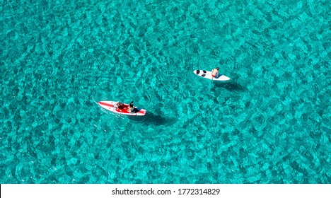 Unrecognizable people having fun with sub boards in the sea, aerial view.