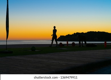 Unrecognizable People on beach at Mount Maunganui at surise in silhouette doing morning fitnes exercise and walking by.