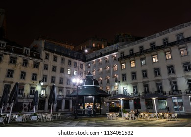 Unrecognizable people on a food kiosk and terrace in the Praça do Municipio square in downtown Lisbon on a clear Winter night.